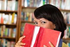 Ragazza asiatica in biblioteca che legge un libro Immagini Stock Libere da Diritti