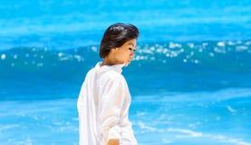 Ragazza asiatica in camicia bianca che sta sulla spiaggia Immagine Stock