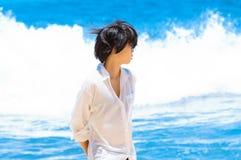 Ragazza asiatica in camicia bianca che sta sulla spiaggia contro il mare Fotografie Stock Libere da Diritti