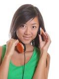 Ragazza asiatica che ascolta la cuffia Immagine Stock