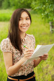 Ragazza asiatica che cattura le note Fotografia Stock
