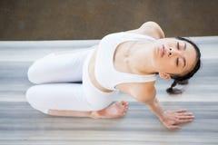 Ragazza asiatica che fa yoga nella posa indietro di piegamento con gli occhi chiusi Fotografia Stock