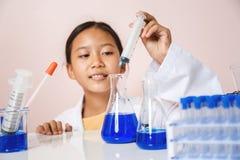 Ragazza asiatica che gioca come scienziato per sperimentare con l'attrezzatura di laboratorio Fotografia Stock Libera da Diritti