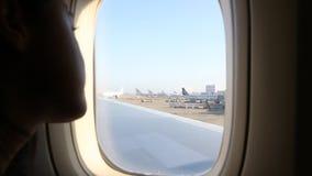 Ragazza asiatica che guarda attraverso la finestra l'aeroporto dall'aeroplano video d archivio