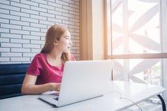 Ragazza asiatica che lavora ad una caffetteria con un computer portatile freelan femminile Fotografia Stock Libera da Diritti