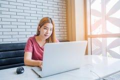 Ragazza asiatica che lavora ad una caffetteria con un computer portatile freelan femminile Fotografie Stock Libere da Diritti
