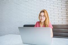 Ragazza asiatica che lavora ad una caffetteria con un computer portatile freelan femminile Fotografia Stock