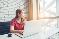 Ragazza asiatica che lavora alla caffetteria con un computer portatile freelan femminile Fotografia Stock Libera da Diritti