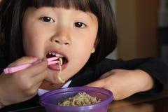 Ragazza asiatica che mangia le tagliatelle Fotografie Stock