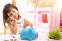 Ragazza asiatica che mette moneta nel porcellino salvadanaio per soldi di risparmio Fuoco selettivo della mano del bambino immagini stock libere da diritti