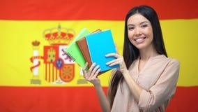 Ragazza asiatica che mostra i quaderni contro il fondo spagnolo della bandiera, imparante lingua archivi video