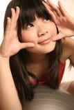 Ragazza asiatica che osserva in su Fotografia Stock