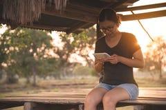 Ragazza asiatica che per mezzo della compressa o dello smartphone Fotografia Stock Libera da Diritti