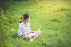 Ragazza asiatica che si siede nel parco sull'erba verde con il computer portatile Immagine Stock