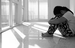 Ragazza asiatica che si siede sul pavimento a casa Oppressione ed isolamento concentrati Fotografia Stock