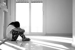 Ragazza asiatica che si siede sul pavimento a casa Oppressione ed isolamento concentrati Fotografie Stock