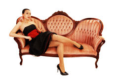 Ragazza asiatica che si siede sul sofà. fotografie stock libere da diritti
