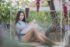 Ragazza asiatica che si siede sul sofà, rilassantesi immagini stock