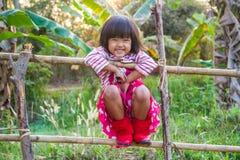 Ragazza asiatica che sorride sul recinto Immagini Stock