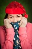 Ragazza asiatica con freddo rosso di tatto del cappello di natale Immagini Stock Libere da Diritti
