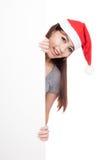Ragazza asiatica con il cappello di Santa che dà una occhiata da dietro un segno in bianco Immagini Stock Libere da Diritti