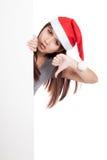 Ragazza asiatica con il cappello di Santa che dà una occhiata da dietro una manifestazione in bianco del segno Immagini Stock Libere da Diritti