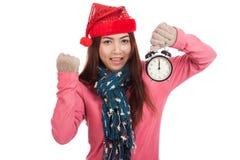 Ragazza asiatica con il cappello rosso di natale eccitato con la sveglia Fotografie Stock Libere da Diritti