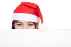 Ragazza asiatica con il cappello rosso di Santa che dà una occhiata dietro un bordo in bianco Fotografie Stock