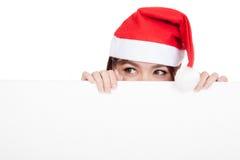 Ragazza asiatica con il cappello rosso di Santa che dà una occhiata dietro un bordo in bianco Fotografia Stock