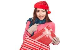 Ragazza asiatica con il contenitore di regalo di tirata del cappello di natale dal sacchetto della spesa Fotografia Stock