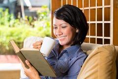 Ragazza asiatica con il libro di lettura della tazza Immagini Stock