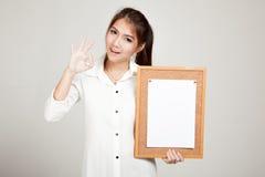Ragazza asiatica con il perno della carta in bianco sul bordo del sughero Fotografie Stock