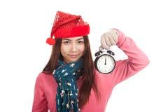 Ragazza asiatica con la sveglia rossa di manifestazione del cappello di natale Immagini Stock