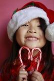 Ragazza asiatica con le canne di caramella ed il cappello della Santa Immagine Stock Libera da Diritti