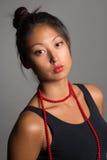 Ragazza asiatica con le perle rosse Fotografie Stock