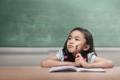 Ragazza asiatica confusa con il libro e penna che fa il suo compito Immagini Stock