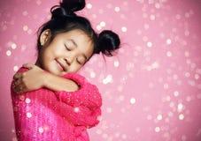 Ragazza asiatica del bambino con gli occhi chiusi nell'abbraccio rosa del maglione e sogno Lustrini dorati fotografia stock
