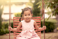 Ragazza asiatica del bambino divertendosi per giocare oscillazione in campo da giuoco Fotografia Stock