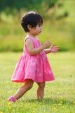 Ragazza asiatica del bambino nel campo verde che osserva in su Immagini Stock