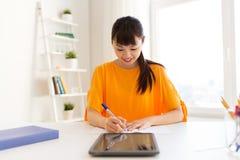 Ragazza asiatica dello studente con il pc della compressa che impara a casa Fotografia Stock