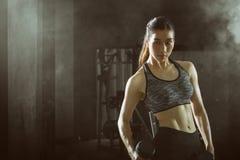 Ragazza asiatica di forma fisica con l'allenamento perfetto del corpo di forma che solleva una testa di legno nella palestra Immagini Stock