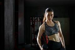 Ragazza asiatica di forma fisica con l'allenamento perfetto del corpo di forma che solleva una testa di legno nella palestra Immagine Stock Libera da Diritti