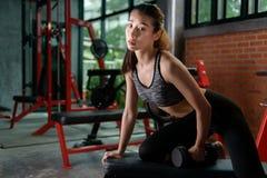Ragazza asiatica di forma fisica con l'allenamento perfetto del corpo di forma che solleva una testa di legno nella palestra Fotografia Stock Libera da Diritti