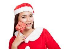Ragazza asiatica di Natale con i vestiti di Santa Claus ed il contenitore di regalo rosso Fotografia Stock Libera da Diritti