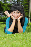 Ragazza asiatica esotica che sorride e che si trova giù Fotografie Stock Libere da Diritti