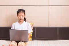 Ragazza asiatica felice che per mezzo del taccuino del computer portatile del computer Immagini Stock