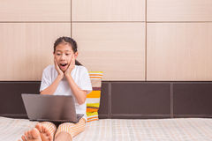 Ragazza asiatica felice che per mezzo del taccuino del computer portatile del computer con la sorpresa ex Immagine Stock