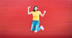 Ragazza asiatica felice che salta mentre musica d'ascolto all'aperto - donna cinese pazza divertendosi ballando una canzone contr fotografie stock