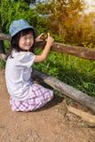 Ragazza asiatica felice che sorride e che si rilassa all'aperto di giorno, t Immagini Stock