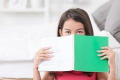 Ragazza asiatica felice con il Libro verde che si nasconde dietro un libro Immagini Stock